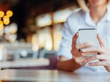 Woman holding mobile phone in a cafe